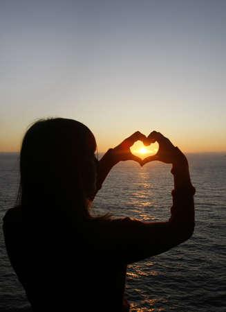 corazon en la mano: forma de coraz�n hecho con una ni�a de las manos al ponerse el sol Foto de archivo