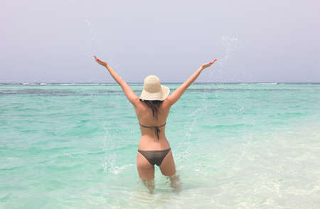 young woman in caribbean sea with open hands