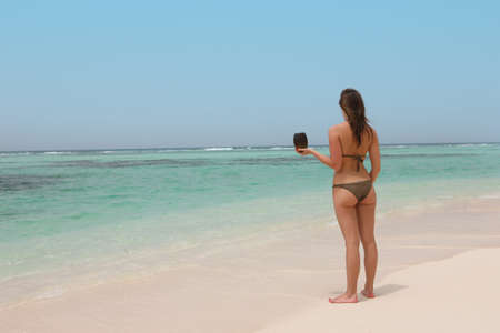 beautiful woman in a tropical beach holding a coconut