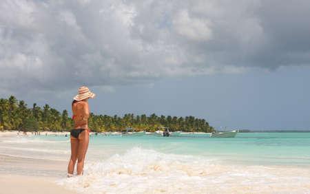 girl looking to the horizon in saona beach Standard-Bild