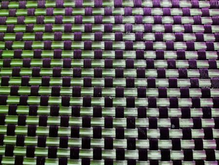 Mexican handmade design, plastic woven in green colors with black, textured background
