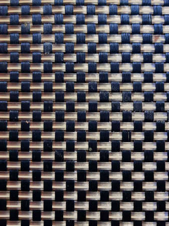 Mexican handmade design, plastic woven in brown colors with black, textured background