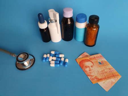 Philippine banknote of twenty pesos, stethoscope, medicine bottles and pills on the blue background