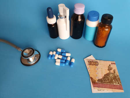 Russian banknote of 100 rubles, stethoscope, medicine bottles and pills on the blue background Фото со стока