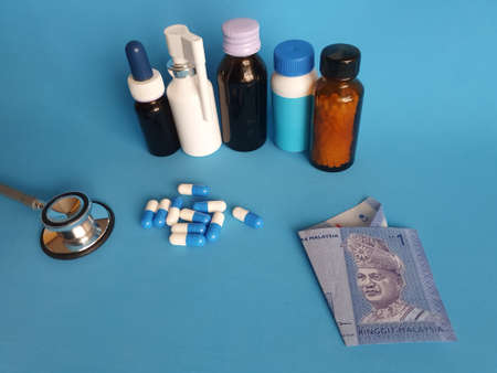 Malaysian banknote of one ringgit, stethoscope, medicine bottles and pills on the blue background Фото со стока