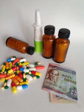 Jamaican banknote of fifty dollars, medicine bottles and pills on the gray background