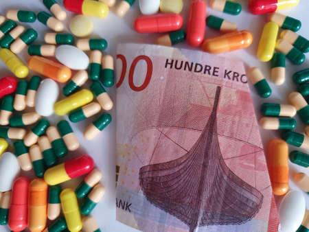 Norwegian banknote of 100 kroner, capsules and medicine pills