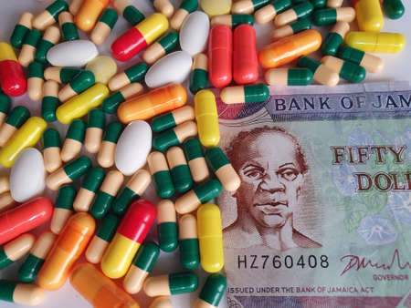 Jamaican banknote of fifty dollars, capsules and medicine pills