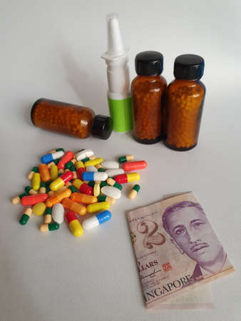 Singaporean banknote of two dollars, medicine bottles and pills on the gray background