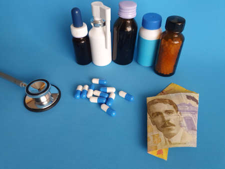 Costa Rican banknote of 5000 colones, stethoscope, medicine bottles and pills on the blue background