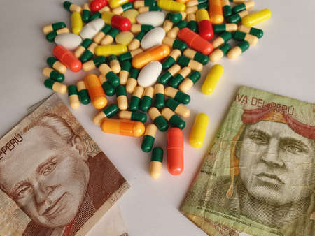 Peruvian banknotes of different denominations, capsules and medicine pills Фото со стока