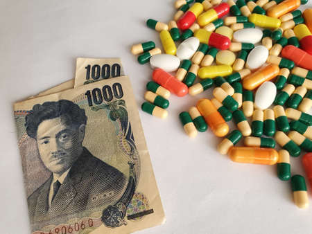 Japanese banknote of 1000 yen, capsules and medicine pills