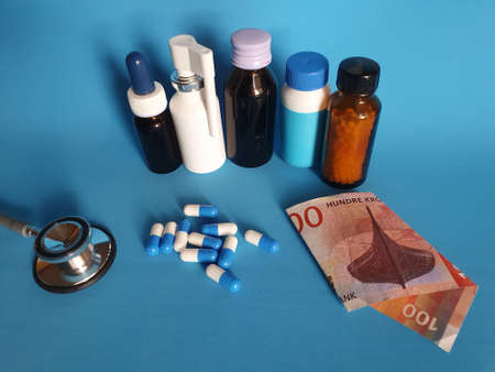 Norwegian banknote of 100 kroner, stethoscope, medicine bottles and pills on the blue background Фото со стока