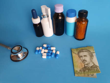 Chilean banknote of 1000 pesos, stethoscope, medicine bottles and pills on the blue background Фото со стока