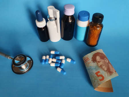 New Zealand banknote of five dollar, stethoscope, medicine bottles and pills on the blue background Фото со стока