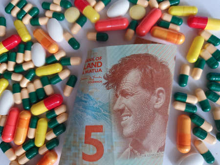 New Zealand banknote of five dollars, capsules and medicine pills