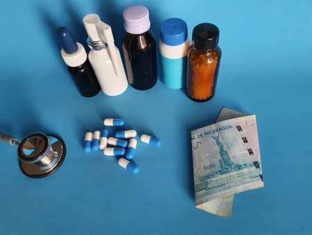 Nicaraguan banknote of 100 cordobas, stethoscope, medicine bottles and pills on the blue background