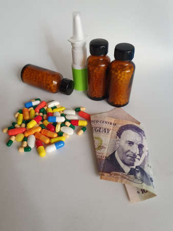 Uruguayan banknote of 100 pesos, medicine bottles and pills on the gray background