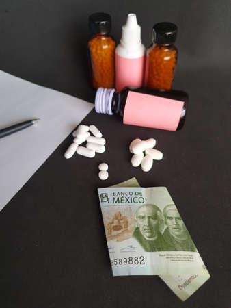 Mexican banknote of 200 pesos, sheet of paper, black pen, medicine bottles and pills Фото со стока