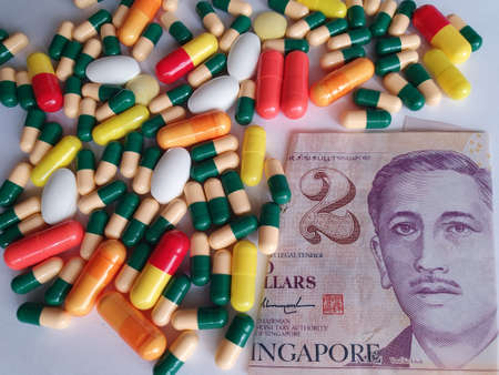 Singaporean banknote of two dollars, capsules and medicine pills