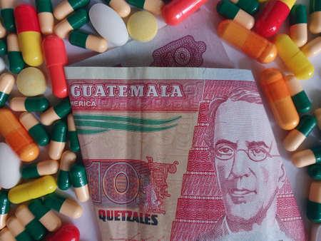 Guatemalan banknote of ten quetzales, capsules and medicine pills