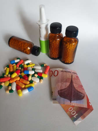 Norwegian banknote of 100 kroner, medicine bottles and pills on the gray background