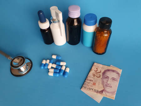Singaporean banknote of two dollars, stethoscope, medicine bottles and pills on the blue background