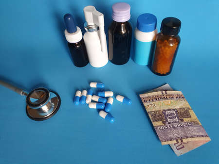 Honduran banknote of two lempiras, stethoscope, medicine bottles and pills on the blue background Фото со стока