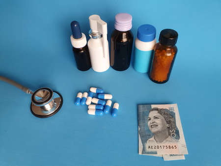 Colombian banknote of 2000 pesos, stethoscope, medicine bottles and pills on the blue background
