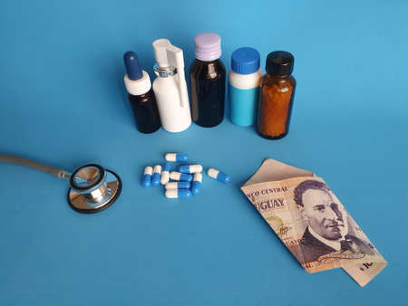 Uruguayan banknote of 100 pesos, stethoscope, medicine bottles and pills on the blue background Фото со стока