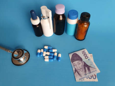 South Korean banknote of 1000 won, stethoscope, medicine bottles and pills on the blue background
