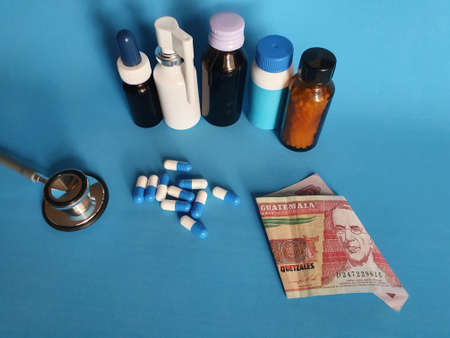 Guatemalan banknote of ten quetzales, stethoscope, medicine bottles and pills on the blue background Фото со стока