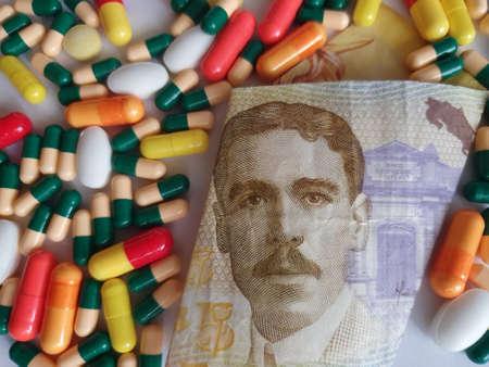 Costa Rican banknote of 5000 colones, capsules and medicine pills Фото со стока