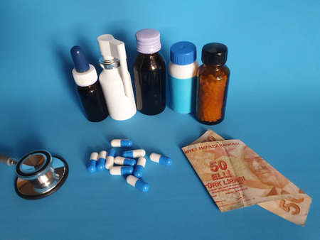 Turkish banknote of fifty lira, stethoscope, medicine bottles and pills on the blue background