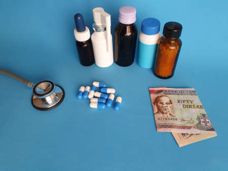 Jamaican banknote of fifty dollars, stethoscope, medicine bottles and pills on the blue background