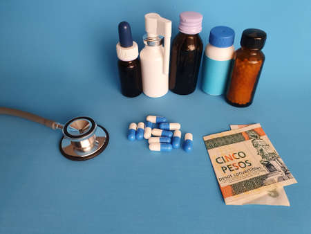 Cuban banknote of five pesos, stethoscope, medicine bottles and pills on the blue background Фото со стока