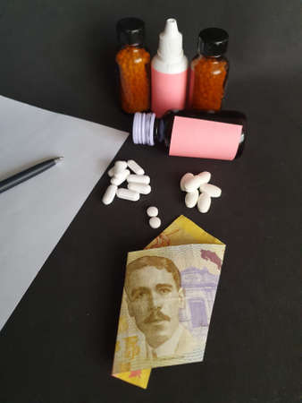 Costa Rican banknote of 5000 colones, sheet of paper, black pen, medicine bottles and pills