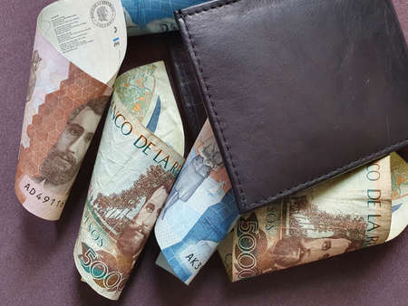 black leather wallet and colombian banknotes of different denominations