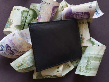 black leather wallet and chinese banknotes of different denominations Stockfoto
