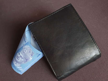 black leather wallet and malaysian banknote of one ringgit