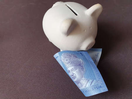 white piggy bank and malaysian banknote of one ringgit Stockfoto