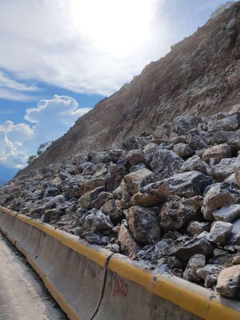 Rocks blocking part of the road in a landslide area during the rainy season