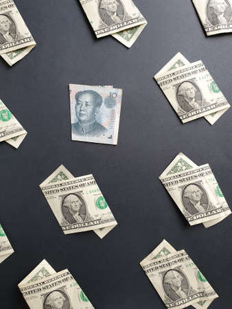 american one dollar bills and chinese banknote of ten yuan on the black background Banco de Imagens