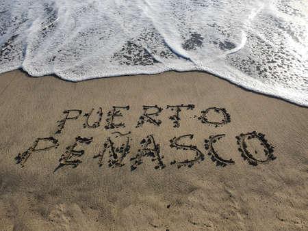 Puerto Penasco text handwritten in beach sand, background and texture