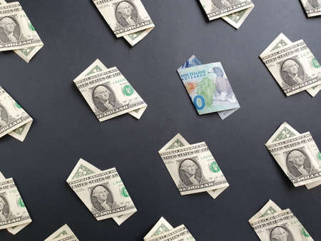 american one dollar bills and New Zealand banknote of ten dollars on the black background
