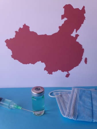 medicine bottle, mask, syringe, and background with a map of China in sheet of paper