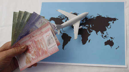 hand holding Chilean money and figure of an airplane on a world map