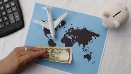 hand holding Nepalese money and figure of an airplane on a world map
