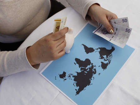 hands of a woman holding danish money and a world map on the table