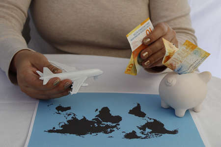hands of a woman holding swiss money and plastic airplane with a piggy bank and a world map on the table Foto de archivo